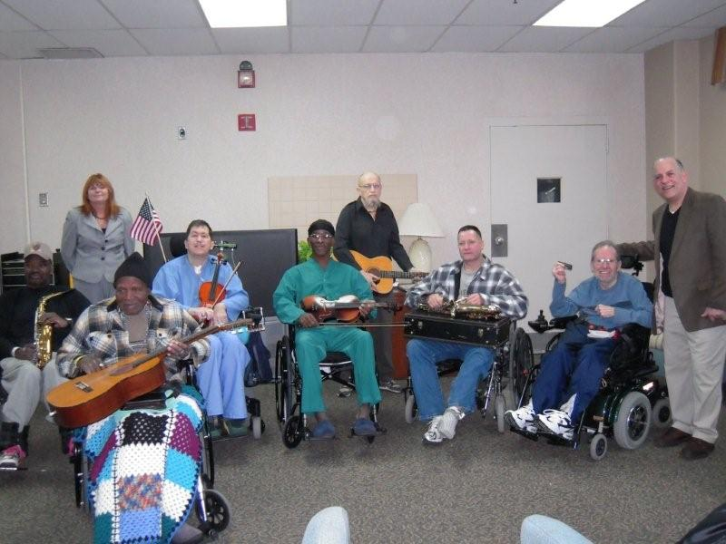 Lou Tansky poses with veterans at the Louis Stokes Medical center. The Veterans hold guitars and other instruments that will be used for music therapy sessions.