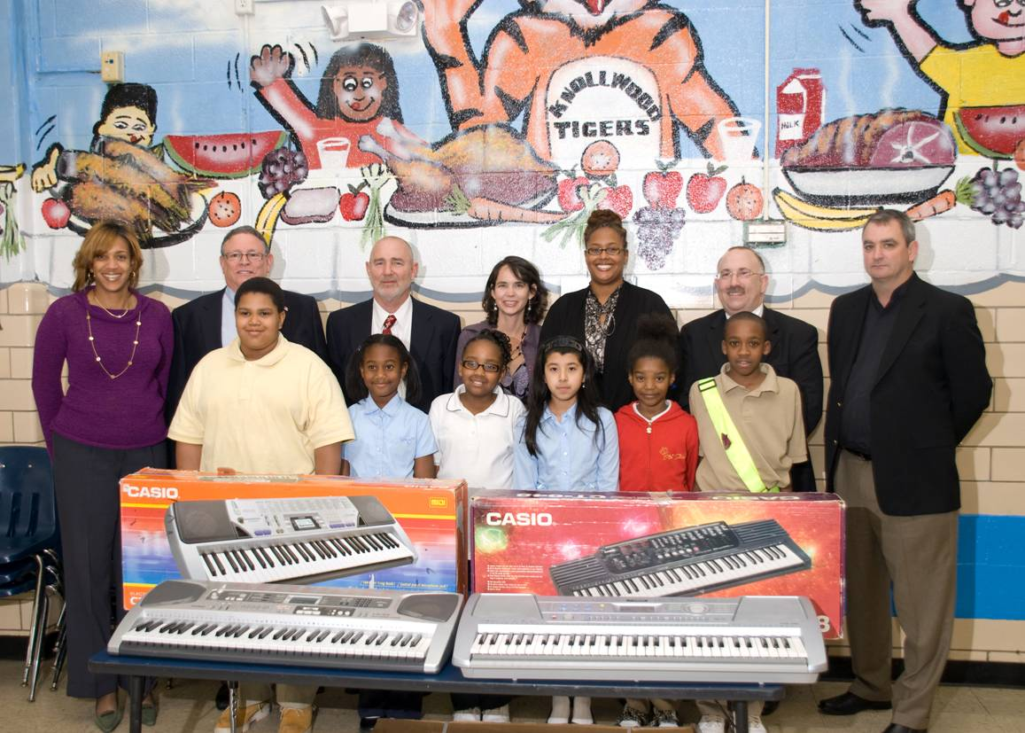 NPA Members stand with students of Knollwood Elementary School along with two new donated keyboards.
