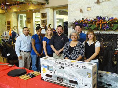A group of Gift Day donors stand with a large keyboard and other instruments they have donated.