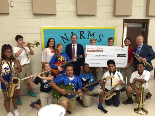 Douglas Braswelll of Braswell & Son Pawnbrokers in Little Rock, Arkansas with large donation check and school faculty, staff and students holding donated musical instruments.